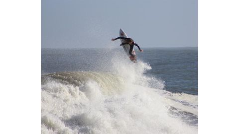 Surfers ride strong waves